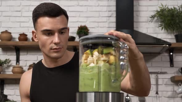 Making Green Juice at Home Athletic Man in Sportswear Blending Healthy Green Smoothie in a Blender