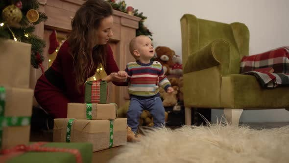 Thumbnail for Cute Joyful Cheerful Mother and Baby Spend Their Leisure Time Next To the Christmas Tree at Home