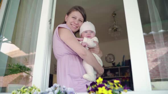 Family Mother Woman With Newborn Baby In The Window Of Her Home