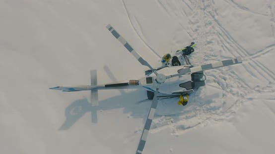 Cover Image for Skiers Boarding a Heliskiing Helicopter Standing in the Snow