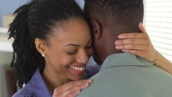Thumbnail for Young black couple embracing and talking to one another