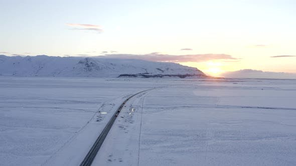 Thumbnail for High Over Snow White Landscape with Road with Cars in Iceland Winter, Sunset, Arctic