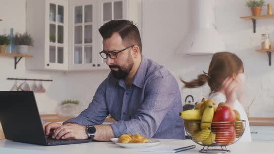 Cover Image for Man Working on His Laptop in the Kitchen