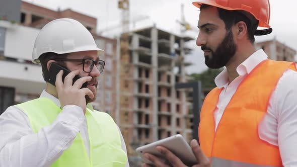 Thumbnail for Happy Engineer Speaks on Mobile Phone on Construction Site and Checks the Work of the Worker