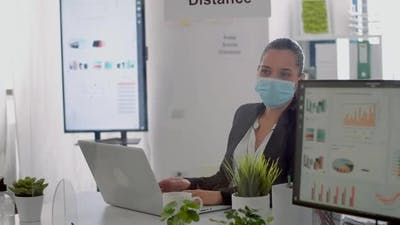 Executive Manager with Face Mask Typing Marketing Information