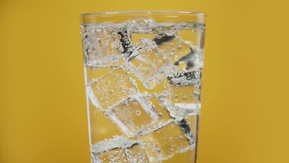 Thumbnail for Glass Full of Cold Sparkling Water with Ice Cubes Yellow Background