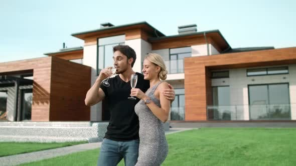 Thumbnail for Rich Couple Drinking Champagne Near House. Smiling People Hugging Outside Villa