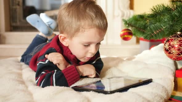 Thumbnail for Little Boy Using and Playing on Digital Computer While Lying Next To christmas Tree
