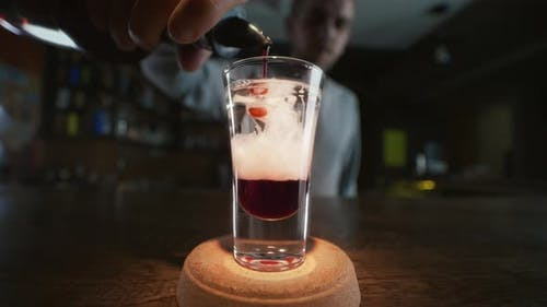 Barman Adds Whine Sirop To the Layered Shot with Red Liquor and Gin in Slow Motion, Making Cocktails