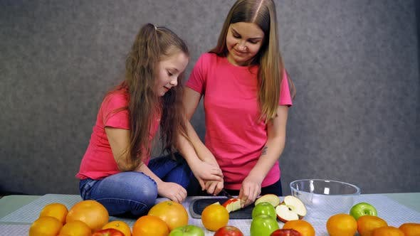 Thumbnail for Girl making fruit salad. Girls sliced fruits for salad at the table