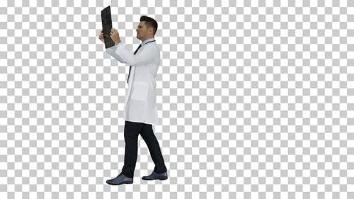 Healthcare personnel in white labcoat looking at x-ray radiographic