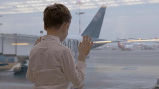 Thumbnail for Child Waiting for Flight and Looking at Planes Through the Window