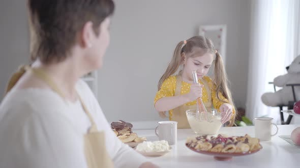 Serious Little Girl Beating Ingredients in Bowl and Smiling To Blurred Woman at the Foreground