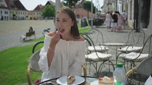 Girl Enjoying Dessert in Outside Cafe