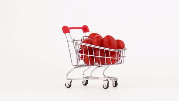 Thumbnail for Moving Supermarket Trolley Packed With Red Cherry Tomatoes Pile. Isolated on the White Background