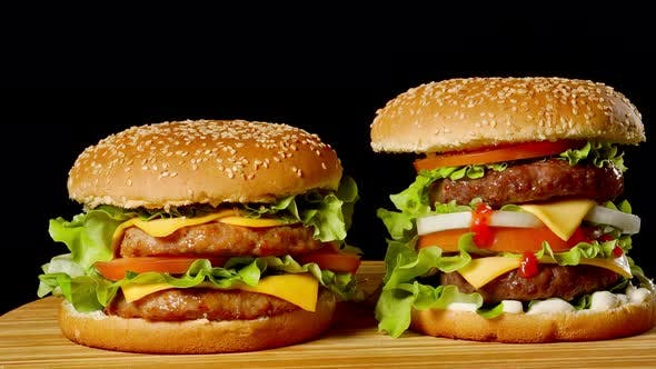 The Concept of American Fast Food. Juicy American Burger with Two Beef Cutlets, with Sauce and