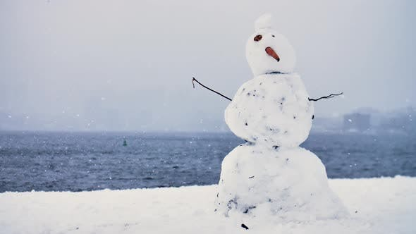 Thumbnail for Funny Dirty Deformed Snowman Carrot Nose Lake Background Winter Snow Storm Large Snowflakes