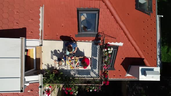Aerial view of family having breakfast on rooftop balcony.