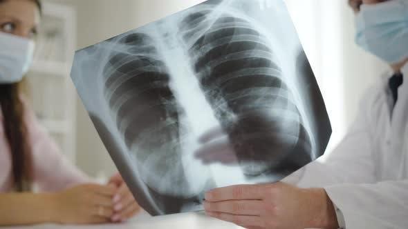 Nahaufnahme Lungen Röntgen mit Arzt und Patient in Gesichtsmasken Sprechen im Hintergrund.  Arzt
