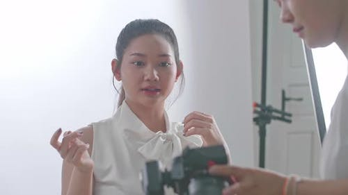 Young Asian Female Photographer Showing Photos To The Asian Model In Studio