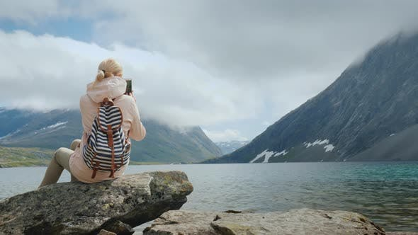 Thumbnail for A Woman Takes a Picture of a Scenic View of a High-mountainous Norwegian Lake