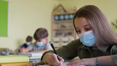 Video of school children and teacher in classroom during a pandemic.