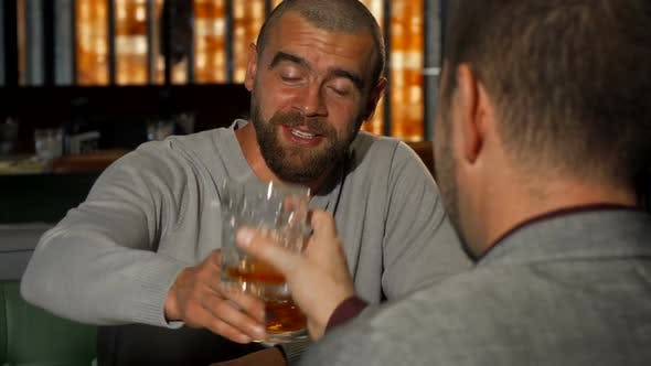 Thumbnail for Handsome Man Clinking Whiskey Glasses with His Friend at the Bar