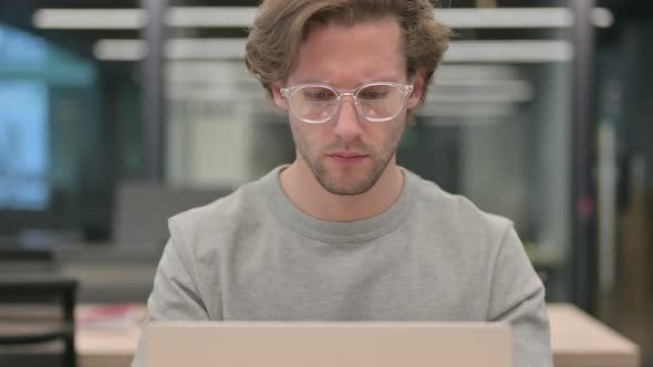 Portrait of Businessman Working on Laptop in Office