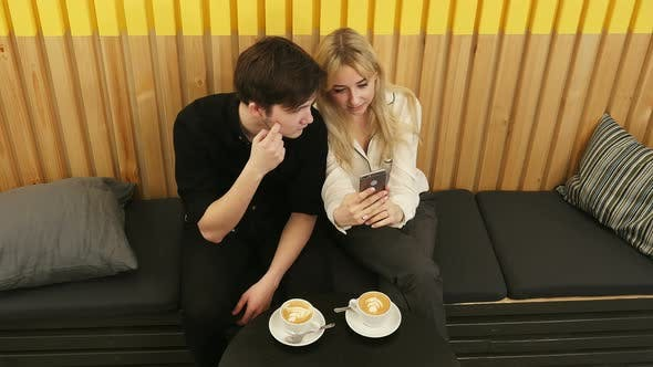 Thumbnail for Happy Couple Using Smartphone Together and Drinking Coffee in Cafe