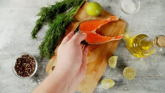 The Men's Hand Puts Raw Pieces of Salmon on Cutting Board.