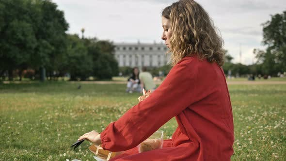 Young Woman Wipes Lips Eating Sandwich in Sunny City Park