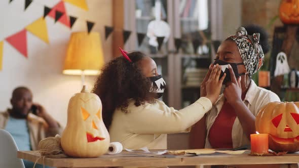 Black Mother and Daughter Making Spooky Halloween Masks