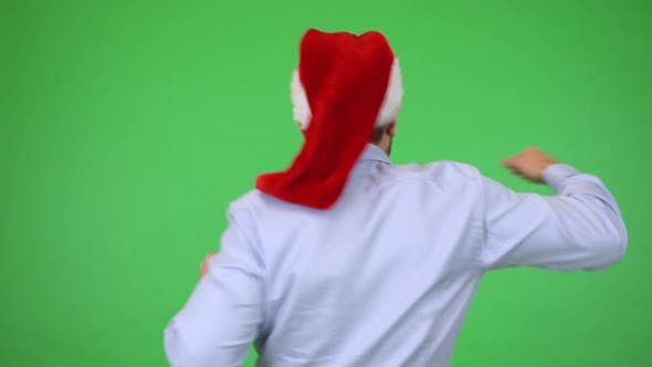 Thumbnail for A Young Handsome Man in a Christmas Hat Celebrates with His Back To the Camera - Green Screen Studio