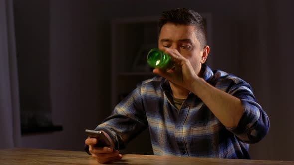 Thumbnail for Man with Smartphone Drinking Bottled Beer at Night 56
