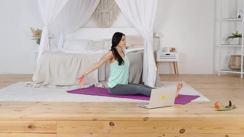 Peacful Happy Young Woman Practicing Yoga on Mat with Laptop