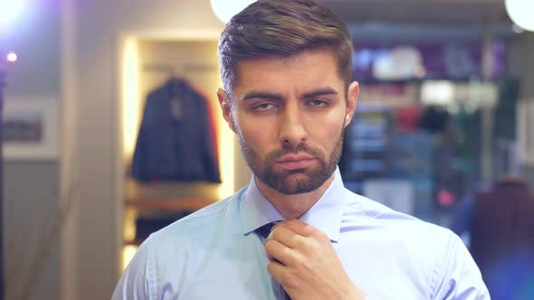 Thumbnail for Man Tying a Tie at Wear Store