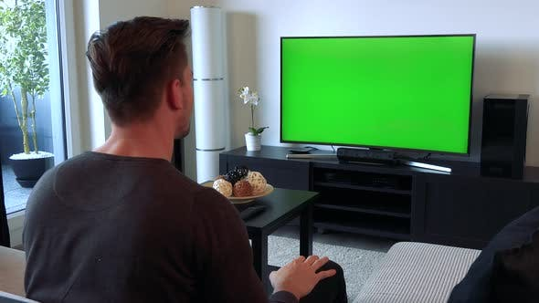 Thumbnail for A Man Cheers and Gesticulates Excitedly at a TV with a Green Screen