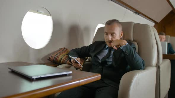Businessman in Formal Suit Traveling on His Private Jet and Chatting on Cell Phone