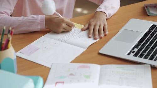 Schulmädchen lernt am Schreibtisch Schreiben Hausaufgaben Fernstudium mit Laptop