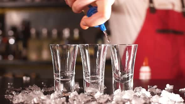 Thumbnail for Professional Male Bartender Pouring Alcoholic Drink in a Shot Glasses in a Nightclub