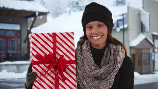 Thumbnail for Happy millennial girl with holiday present looking at camera on snowy street