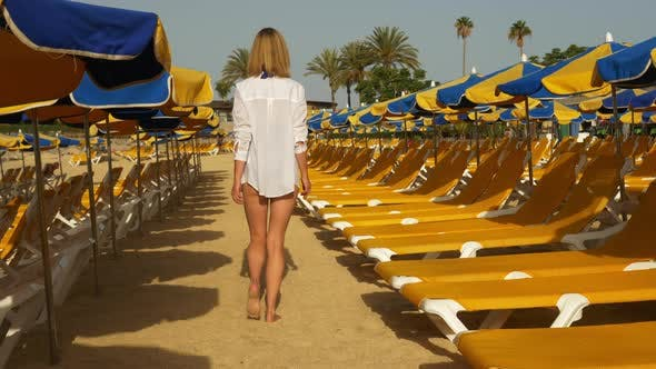 Thumbnail for Blonde Woman Walking Barefoot in the Sand Through Beach Decks