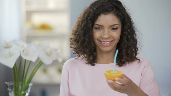 Thumbnail for Healthy Young Woman Holding out Orange with Straw, Developing Immunity