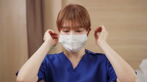 Asian female nurse put protective surgical face mask on to prevent covid virus pandemic in hospital.
