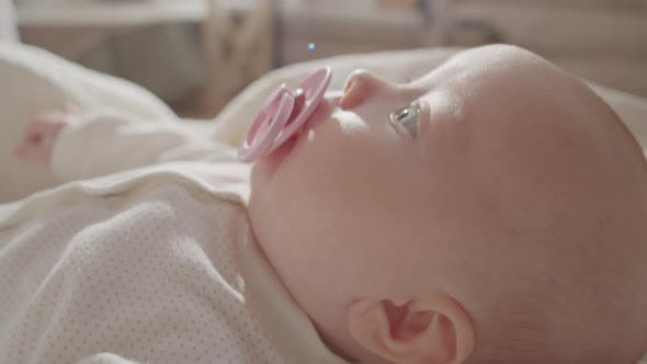 Little Baby with Pacifier Lying on Bed