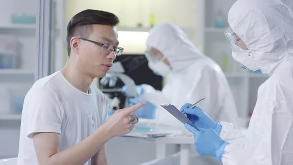 Thumbnail for Asian Man Describing Symptoms to Doctor in Disposable Coveralls