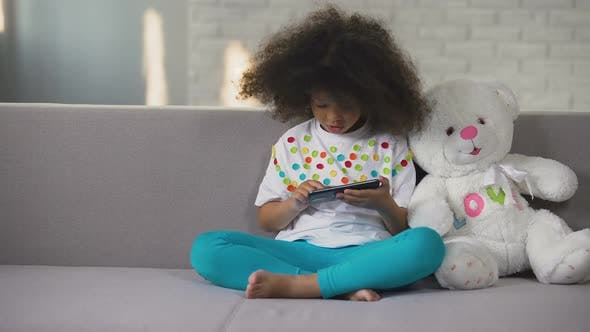 Thumbnail for Afro-American girl sitting on sofa with favourite toy and playing on cellphone