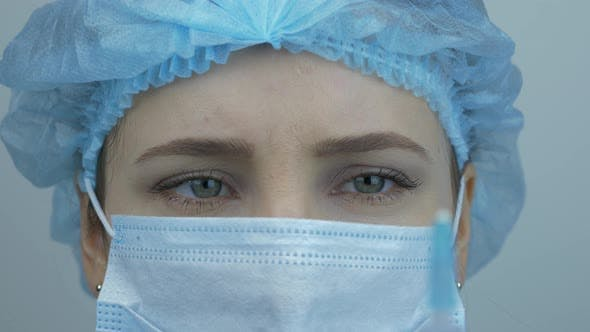 Thumbnail for Nurse face in medical mask and cap is holding syringe with Coronavirus vaccine. Virus protection.