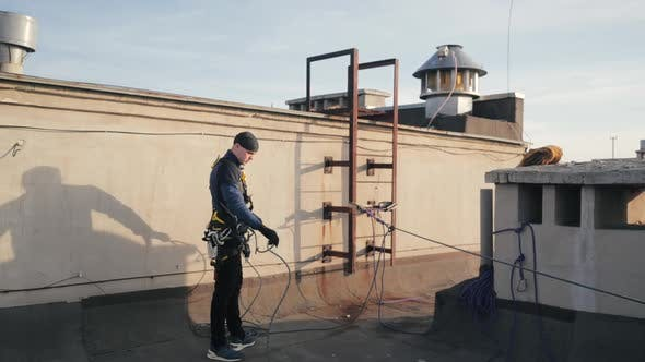 Industrial Climber Man Fastens Rope for Insurance on Rusty Ladder of Roof for Descent Down Outer