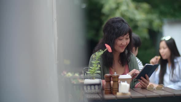 Thumbnail for Asian Woman Writing on Smartphone in Outdoor Restaurant